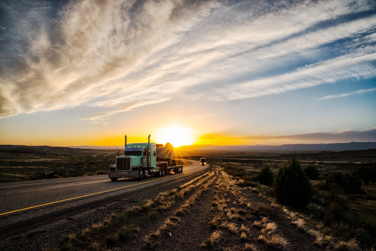 Long Haul Semi Truck on a Highway at Dusk under a Dramatic Sky